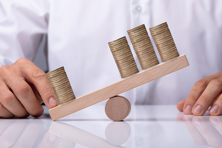 Businessperson's Hand Showing Unbalance Between Stacked Coins On Wooden Seesaw